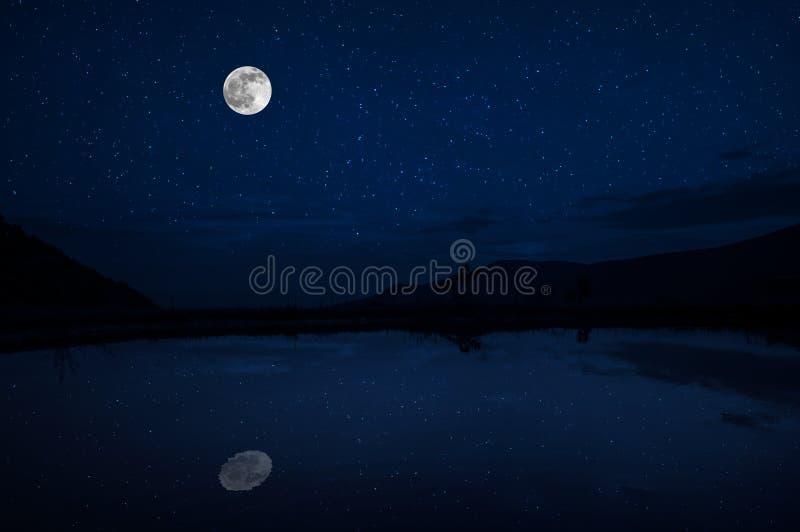 Denna dramatiska månelöneförhöjning i en djupblå nattetidhimmel betonas av markerade moln och härlig lugna sjöreflexion royaltyfri bild
