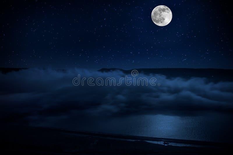 Denna dramatiska m?nel?nef?rh?jning i en djupbl? nattetidhimmel betonas av markerade moln och h?rlig lugna sj?reflexion fotografering för bildbyråer