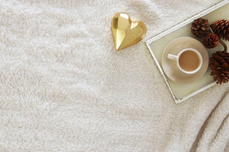 denneappels en kop van cappuccino over comfortabel en bonttapijt Hoogste mening stock afbeelding