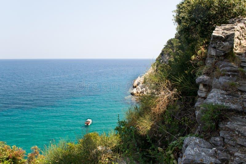 Denny widok na jeden łodzi w seledyn wodzie i kawałku faleza, Doumuchari Laguna, Grecja zdjęcie royalty free
