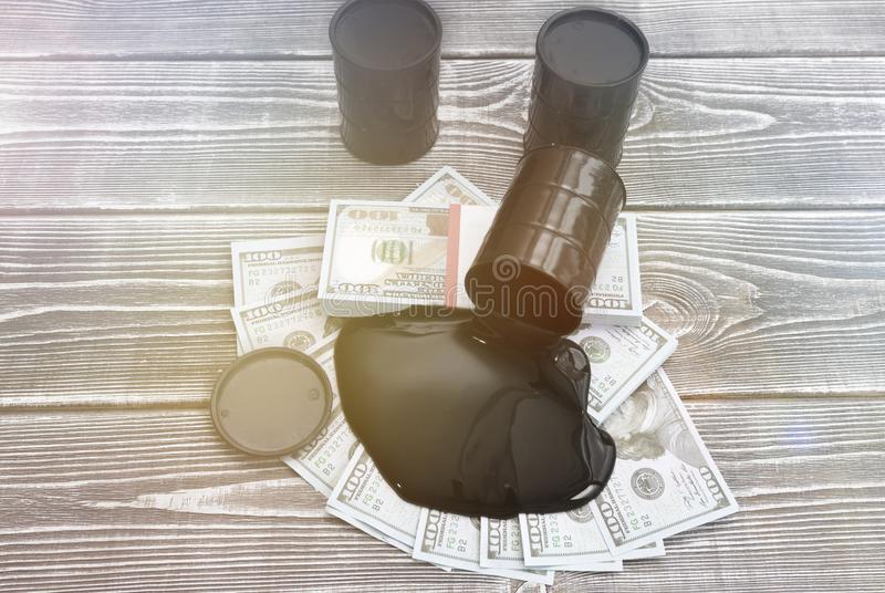 Three barrels of oil, dollars on a wooden background. Denominations of American dollars, barrels of oil on a wooden background. purchase, sale of oil royalty free stock photos