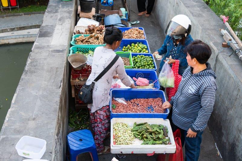 DENPASAR/BALI-, 20. APRIL 2019: Gewürzhändler verkaufen auf der Badungs-Flussbrücke und es gibt auch Käufer, die etwas Paprika ka stockbild