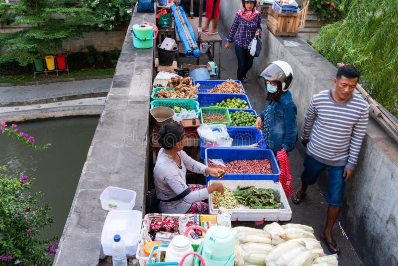 DENPASAR/BALI-APRIL 20 2019: kryddaaff?rsm?n s?ljer p? den Badung flodbron, och det finns ocks? k?pare som k?per n?gon chili och royaltyfri fotografi