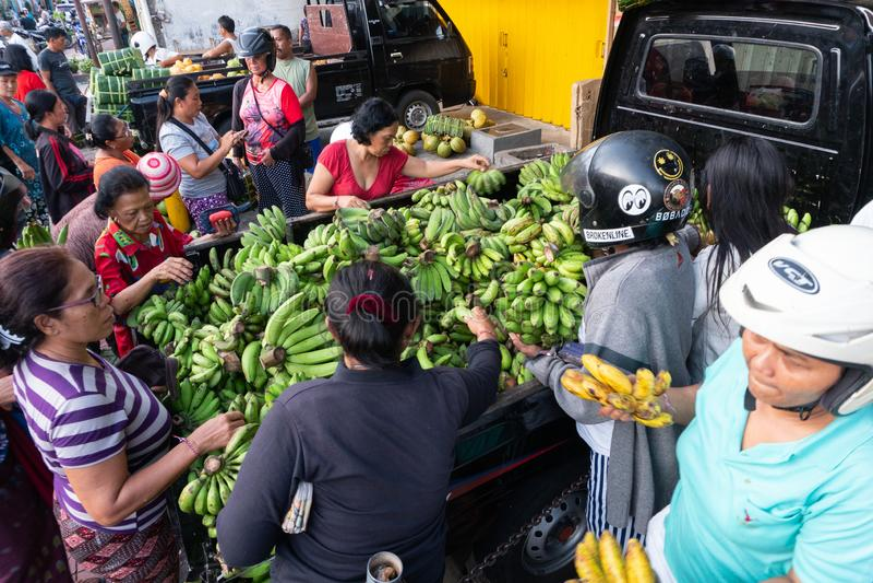 DENPASAR/BALI- 20 APRILE 2019: il venditore verde della banana sta vendendo i suoi articoli su un'automobile in uno degli angoli  immagini stock libere da diritti