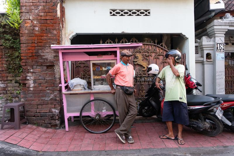 DENPASAR/BALI- 20 AVRIL 2019 : un vendeur de boulette de viande de rue utilise un chariot rose et utilise une chemise rose causan photos libres de droits