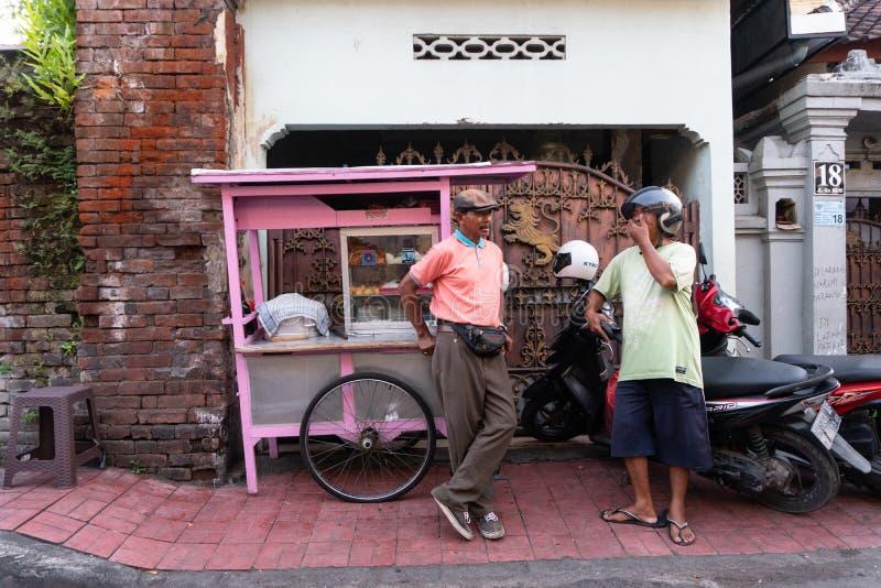 DENPASAR/BALI- 20 DE ABRIL DE 2019: um vendedor da almôndega da rua usa um carro cor-de-rosa e veste uma camisa cor-de-rosa que c fotos de stock royalty free