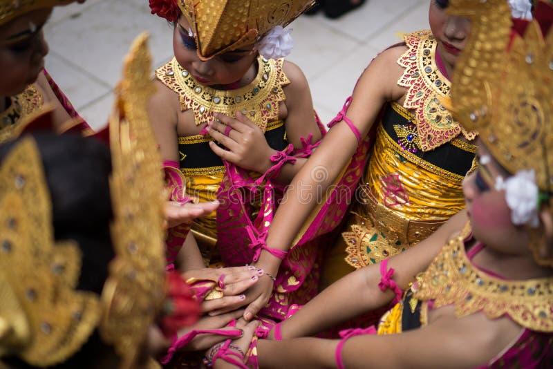 DENPASAR/BALI- 28 DE DICIEMBRE DE 2018: un equipo de bailarines de sexo femenino está llevando a cabo las manos juntas para aumen foto de archivo libre de regalías