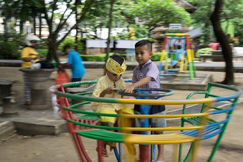 28 denpasar/bali-DECEMBER 2017: twee jongens die op het gazon spelen Één van hen speelt spelen met gadgets, als wordt gewijd aan stock foto's