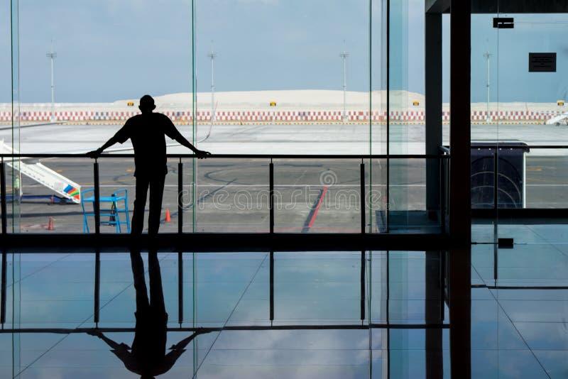 Denpasar, Bali, Indonésia: 5 de junho de 2019 - homem que olha através das janelas de vidro no aeroporto como espera seu voo fotografia de stock royalty free