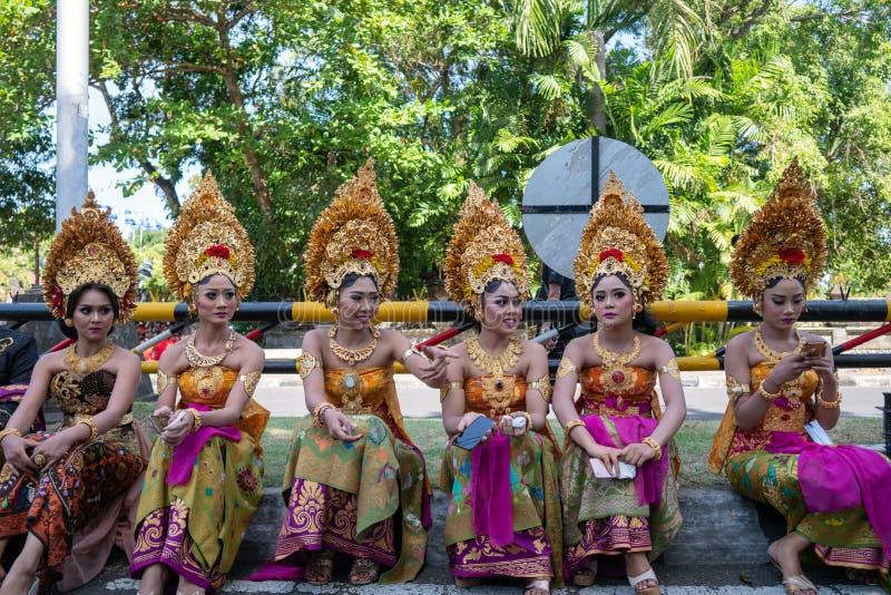 DENPASAR/BALI-JUNE 15 2019年:穿传统巴厘语头饰和传统布裙的年轻巴厘语妇女在开头 免版税图库摄影