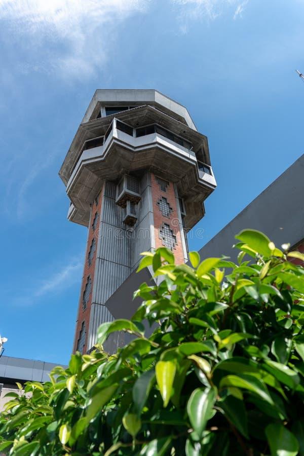 DENPASAR/BALI-, 27. MÄRZ 2019: FlughafenKontrollturm an internationalem Flughafen Bali Ngurah Rais, unter blauem Himmel mit grüne lizenzfreie stockfotografie