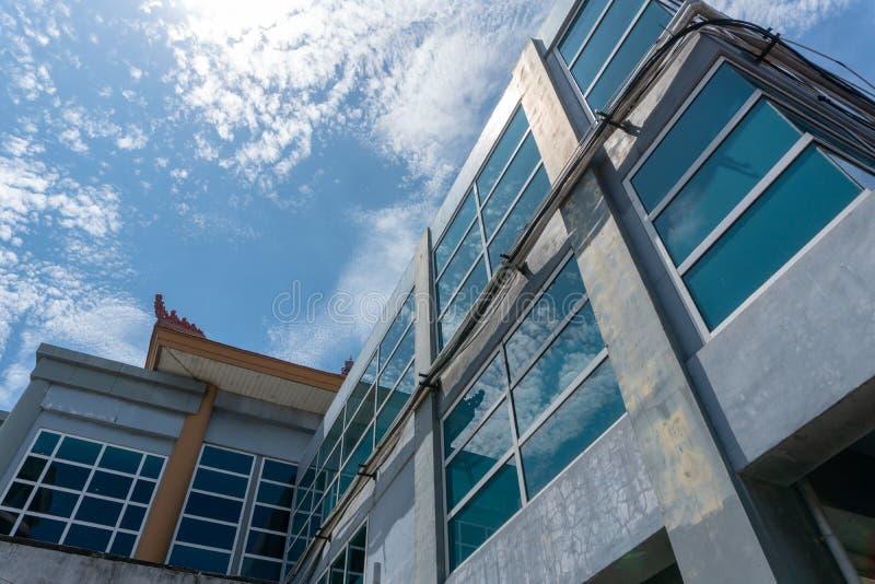 DENPASAR/BALI-, 27. M?RZ 2019: Das Geb?ude mit Glasfenstern benutzt eine kleine Balineseverzierung auf dem Dach w?hrend das sonni stockfotografie