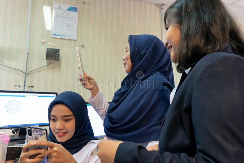 27 denpasar/bali-MAART 2019: De vrouwen die een hijab gebruiken texting op haar cellphone terwijl haar andere haar bekijken en vr royalty-vrije stock afbeeldingen