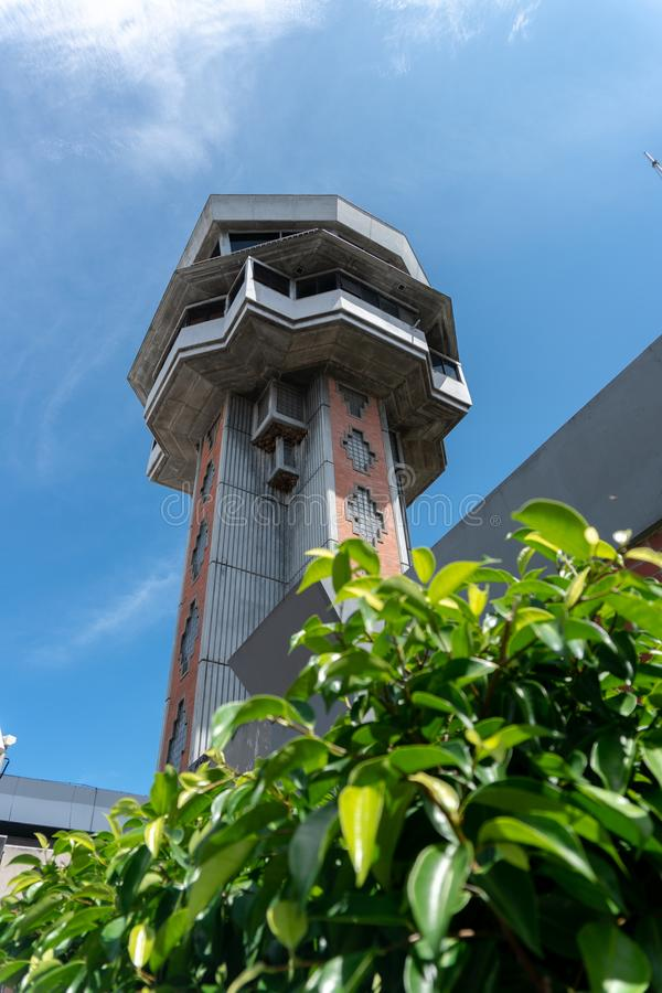 DENPASAR/BALI-MARCH 27 2019: Airport control tower at Ngurah Rai International Airport Bali, under blue sky with green leaf royalty free stock photography