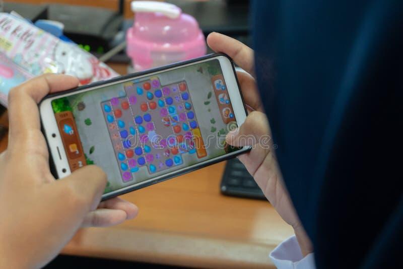 DENPASAR/BALI-MARCH 27 2019: en kvinna som använder en hijab, är kall spela lekar på hennes mobiltelefon, medan vänta på tiden at arkivbilder