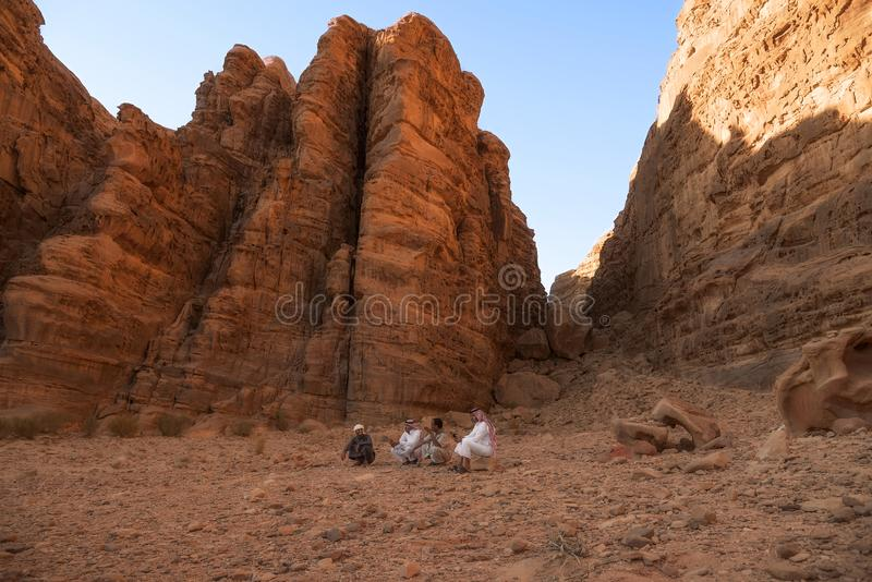 Denrom ökenJordanien 17-09-2017 fyra beduinmän sitter i mitt av öknen på en sten eller en hopkrupen ställning, mellan det höga be fotografering för bildbyråer