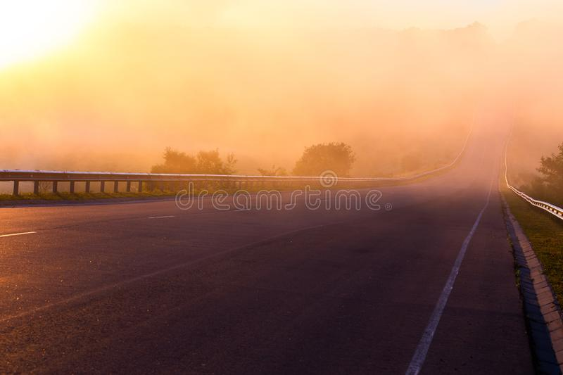 Dense early morning fog in wold at summer highway near river with guard rails. Early morning fog in wold at summer highway near river with guard rails stock images