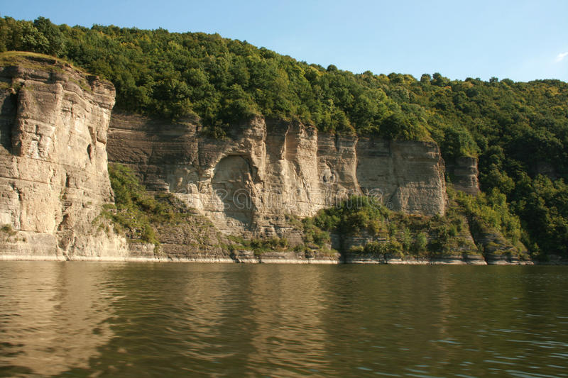 Dense forest on a cliff above the river. As you can see the rock cave. Nice summer weather royalty free stock photography