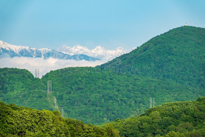 Dense green forest in the valley and on the slopes of the mountain. Power lines in the forest. Snow capped mountains visible on. The horizon. Mount Akhun and royalty free stock photography