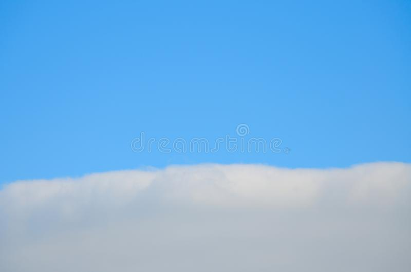 Dense light gray cloud with a horizontal edge. royalty free stock photography