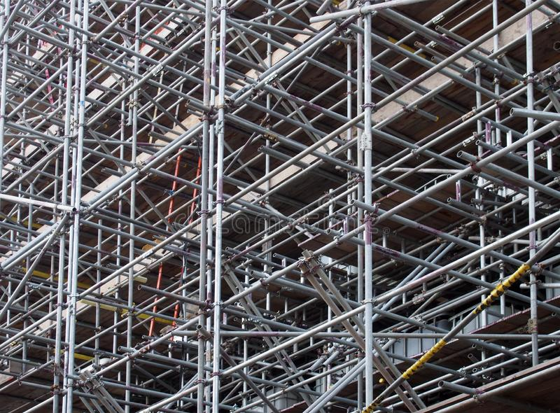 A dense network of metal scaffolding poles supporting work platforms on a construction site stock image