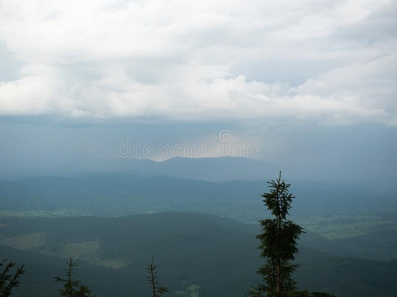 Dense rainy clouds above the green mountain range. Carpathians mountains, west Ukraine. Wild nature landscape. Rainy day. In Carpathians. Heavy downpour in royalty free stock photography