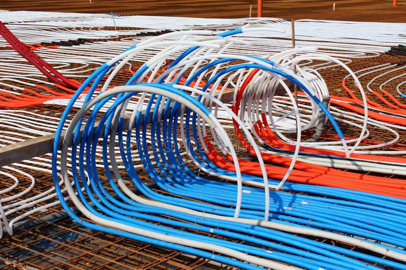 Densely put plastic water pipes endings laid on top of rusted metal construction net for installation of radiant floor heating royalty free stock photos