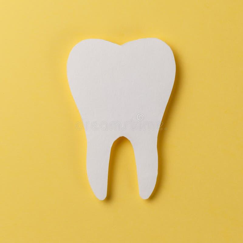 Dent blanche sur le fond jaune photos stock