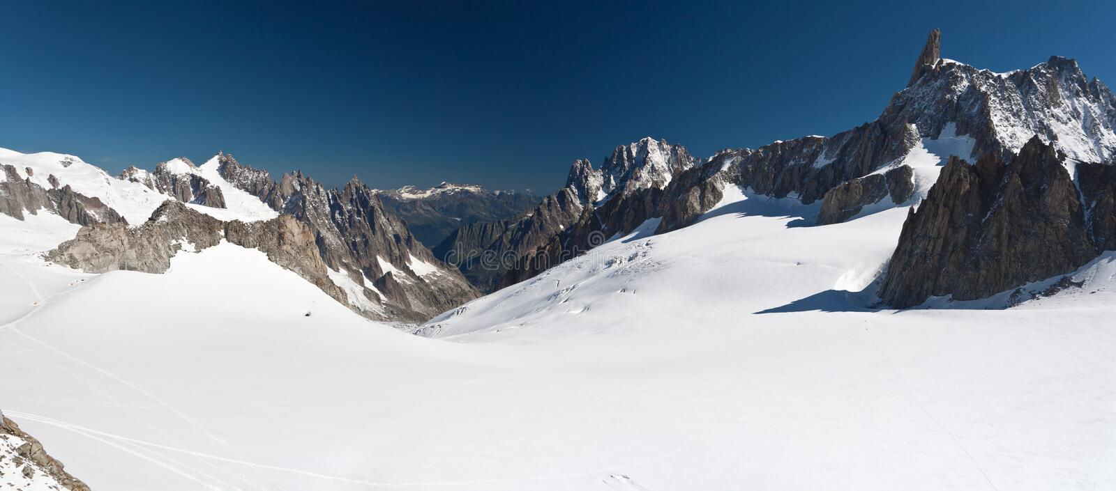 Dent du Geant and mer de glace -. Panoramic view of Dent du Geant peak and glacier in Mont Blanc massif royalty free stock photography