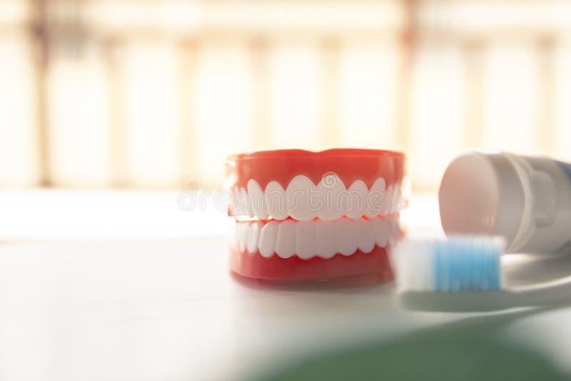 Dentadura ascendente próxima com a escova de dentes do dentífrico no fundo borrado Metáfora para oral, cuidados médicos toothy da fotografia de stock