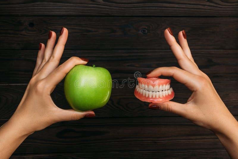 Dentadura de los dientes falsos contra manzana verde del granny smith Cuidado dental de la prótesis Dentadura y Apple en las mano imágenes de archivo libres de regalías