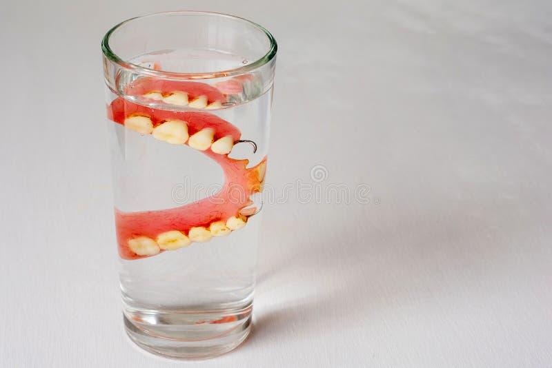 Dentadura en un vidrio con agua en un fondo blanco foto de archivo