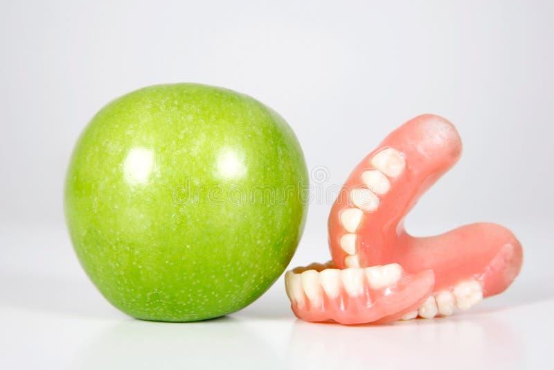 Dentadura y manzana foto de archivo