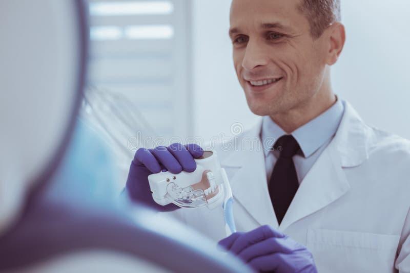 Dentaduras de medición del dentista de sexo masculino hermoso fotos de archivo libres de regalías