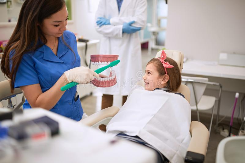 Dental assistant showing to child how to brushing her teeth royalty free stock image