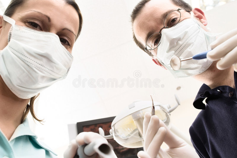 Dental attendance. Dentist and assistant are examining you the patient