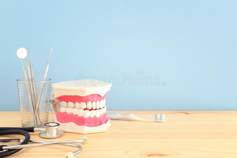 Dental care tools use for dentist and plastic teeth model in the clinic. Wooden blue background. Dental care tools use for dentist and plastic teeth model in royalty free stock image