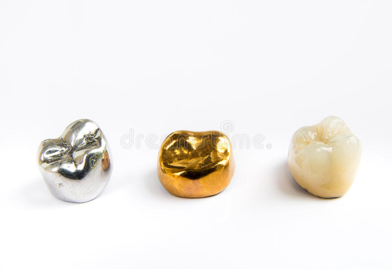 Dental ceramic, gold and metal tooth crowns on white background. royalty free stock images