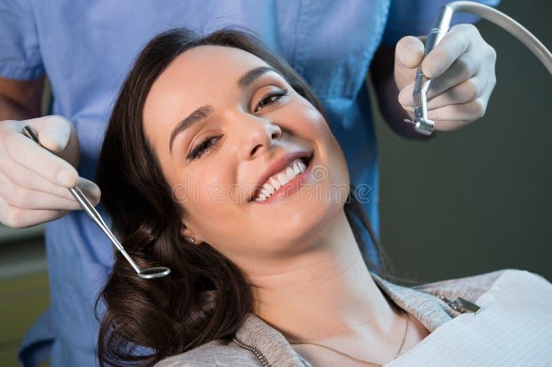 Dental checkup. Smiling young women receiving dental checkup royalty free stock photo