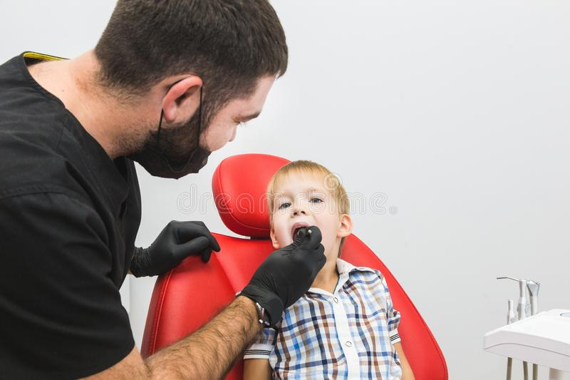Dental clinic. Reception, examination of the patient. Teeth care. Dentist treating teeth of little boy in dentist office royalty free stock photo