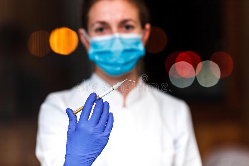 Dental and endodontic instruments in hands of dentist. The dentist women in blue gloves holding metal professional tools stock photography