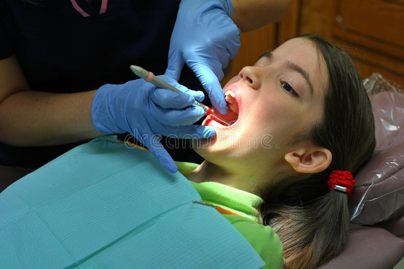 Dental Exam. Young girl gets a dental exam stock images