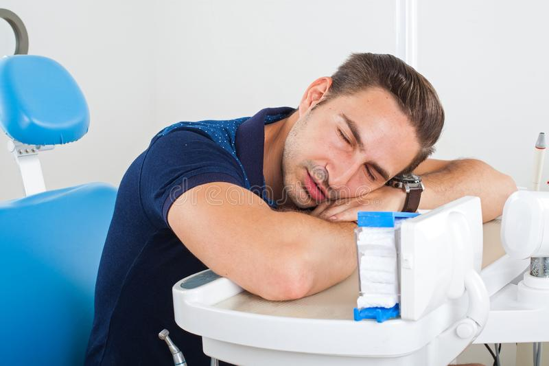 Dental examination. Sleepy patient waiting for a dental examination stock image