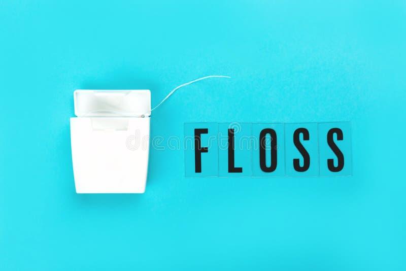 Dental floss on blue pink background stock image