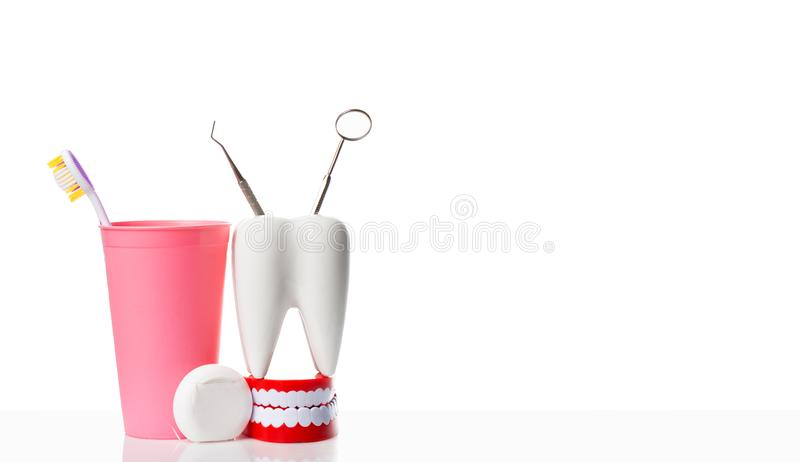 Dental health and teethcare concept. Dental mirror and dental explorer instrument in white tooth model, human jaw and dental floss. Near toothbrush in pink royalty free stock image