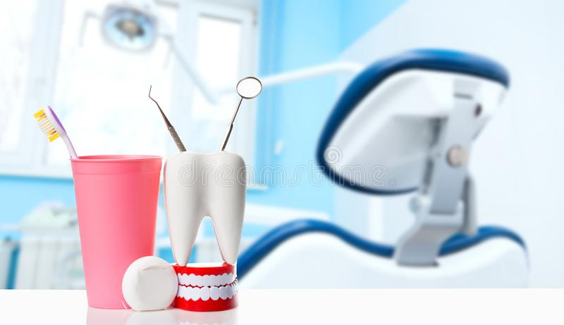 Dental health and teethcare concept. Dental mirror and dental explorer instrument in white tooth model, human jaw and dental floss. Near toothbrush in pink royalty free stock photos