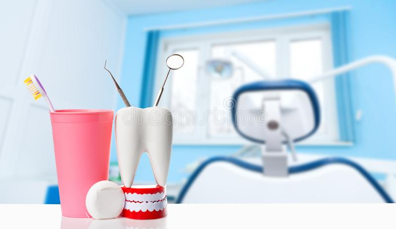 Dental health and teethcare concept. Dental mirror and explorer instrument in white tooth model, human jaw and dental floss near. Toothbrush in pink glass stock photo