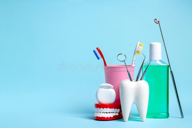 Dental health and teethcare concept. Dental mirror with explorer probes in healthy white tooth model near dental floss, human jaw. Mouthwash and toothbrushes stock photo