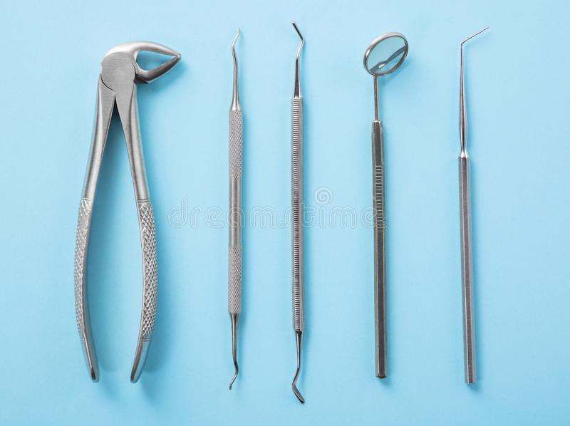 Dental health and teethcare concept. Top view of dental tools set on blue background in dentists clinic: dental mirror, explorers royalty free stock image