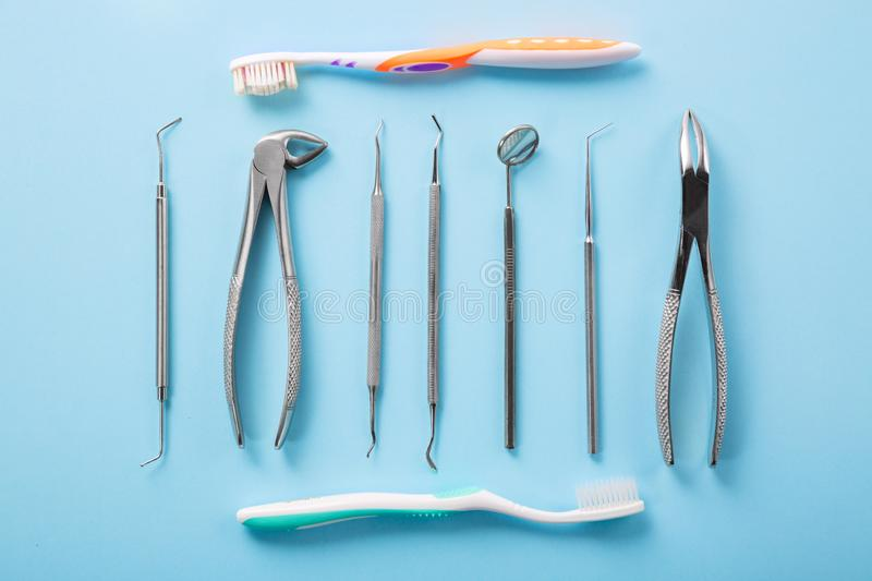 Dental health and teethcare concept. Top view of dental tools set on blue background with toothbrushes in dentists clinic: dental royalty free stock photo